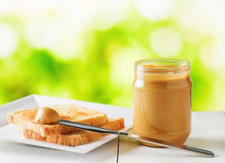 Jar of peanut butter and toasts on nature background. Stock Photo