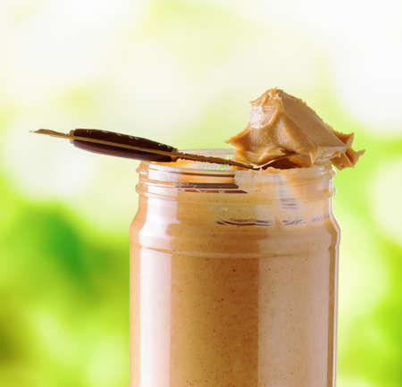 Jar of peanut butter on nature background. photo