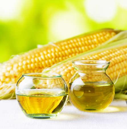 コーン油とトウモロコシの穂軸が庭のテーブル。 写真素材