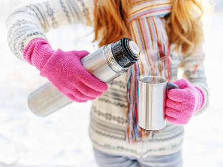 thermos: Woman is pouring a hot drink in mug from thermos. Stock Photo