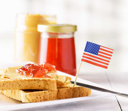 strawberry jelly: Toasts with peanut butter and strawberry jam on white table. American breakfast. Stock Photo