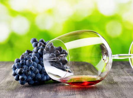 木製のテーブルでブドウとワインのグラス。