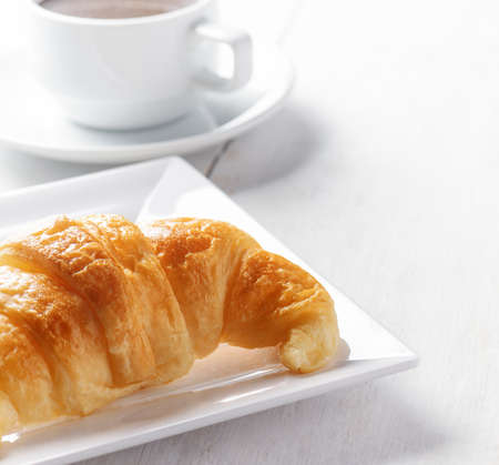Cup of coffee and croissant on white wooden table. photo