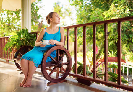Young woman in blue dress enjoying a cup of beverage. Outdoor portrait. Coffee and tea drinking conception. photo