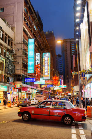 hong kong night: HONG KONG – JANUARY 28, 2015: Taxi on the street of night city. Hong Kong is a leading financial centre of the world.