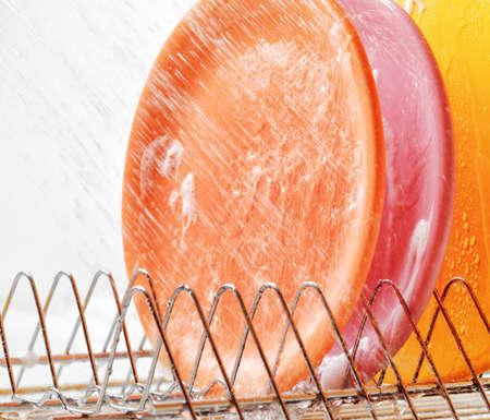 lavar platos: Platos bajo chorros de agua. Lavavajillas y el trabajo dom�stico.