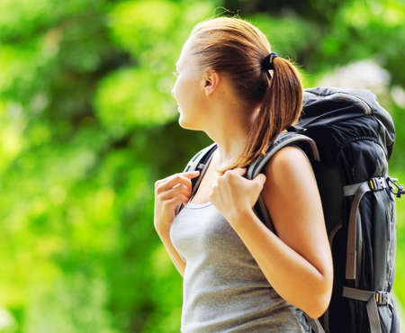camping: Young smiling woman with backpack in a wood. Hair in a bun. Woman wearing grey clothing. Hiking with camping at summer.