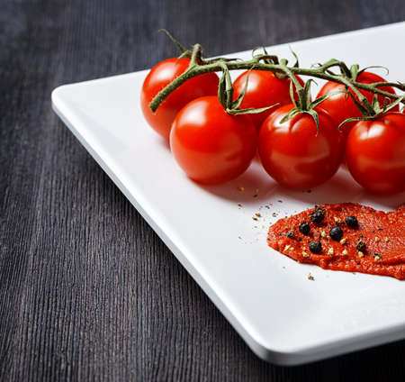 tomato paste: Ripe tomatoes and tomato paste in a white plate on a wooden table