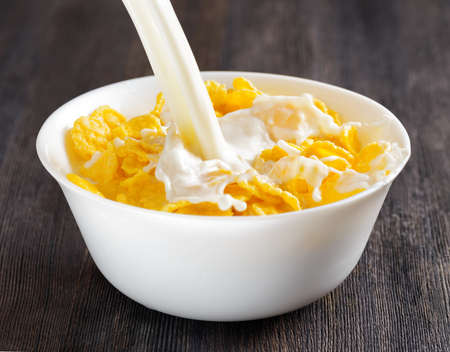 cornflakes: Fresh milk and cornflakes in a white bowl on a wooden table