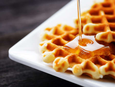 Honey pouring on a fresh waffles. Organic healthy food rich in minerals and vitamins. Eco food for breakfast. Trendy sweet confections.