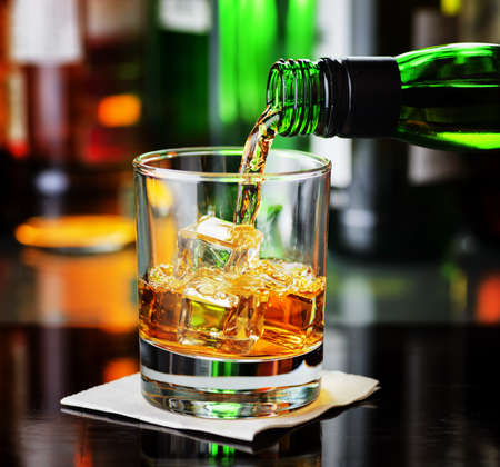 Whiskey pouring from a bottle into a glass in a bar. Scotch and Irish Single Malt or Blended Whiskey classic drinks for real men.
