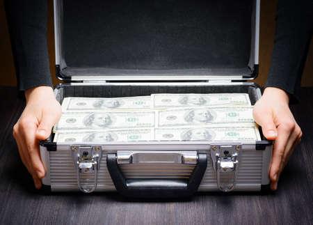 caja fuerte: Almacenamiento y protección de dinero en efectivo y objetos de valor. Concepto de banca. Hombre de negocios que abre un maletín de aluminio llena de fajos de billetes de cien dólares. Dinero en manos seguras. Foto de archivo
