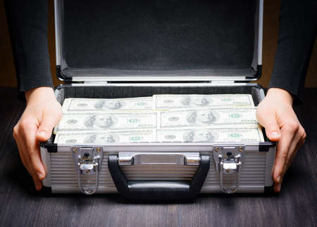 Storage and protection of cash and valuable items. Banking concept. Business man opens an aluminum briefcase full of stacks of hundred-dollar bills. Money in safe hands.