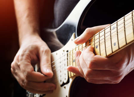 Man playing guitar on a stage. Musical concert. Close-up view. Live rock stars performing musical hits. Guitar solo in the spotlight. Musician pluck the strings with the help of a plectrum.