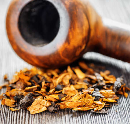 blends: Aromatic leaves of pipe tobacco on a black wooden table and pipe in the background. Smoking accessories, tobacco blends. Shallow depth of field. Stock Photo