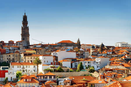 torre: Colored facades and roofs of houses in Porto, and the bell tower of Torre dos Clerigos. It is a popular tourist attraction of Portugal. Stock Photo
