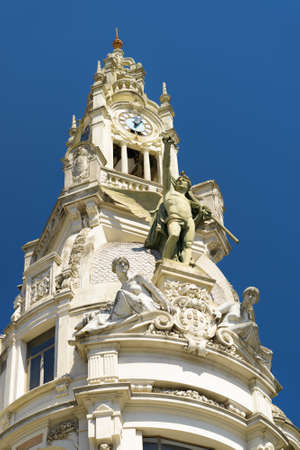 adorn: The clock tower and sculptures that adorn the facade of building in Porto, Portugal. Porto is one of the most popular tourist destinations in Europe.