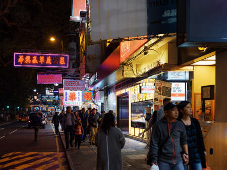 outdoor advertising: HONG KONG - JANUARY 30, 2015: Pedestrians and illuminated signs on the street of night city. Hong Kong is popular tourist destination of Asia and leading financial centre of the world.