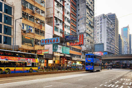 hongkong: HONG KONG - JANUARY 31, 2015: Decker buses and trams on the central streets. Hong Kong is popular tourist destination of Asia and leading financial centre of the world.