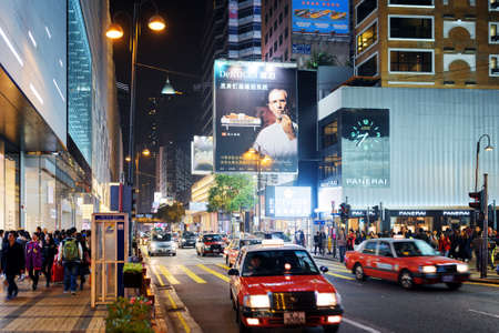 taxi famous building: HONG KONG - JANUARY 31, 2015: Taxi and illuminated signs on streets of night city Hong Kong. Hong Kong is a popular tourist attraction of Asia and leading financial centre of the world. Editorial