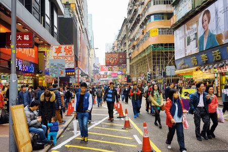 HONG KONG - 1 februari 2015: Voetgangers op de straten van de stad Hong Kong. Hong Kong is een populaire toeristische attractie van Azië en de belangrijkste financiële centrum van de wereld. Redactioneel