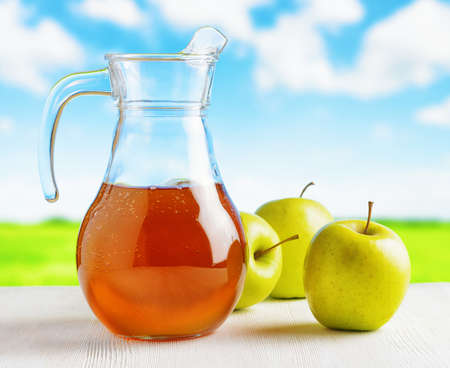 fresh juice: Jug of apple juice and green apples on meadow background. Eco food rich in minerals and vitamins. Product of organic farming. Stock Photo
