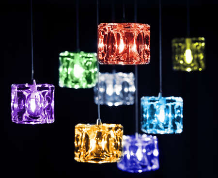 light fixture: Closeup view of contemporary light fixture on a dark background. Small colorful bright lights creating a festive and romantic atmosphere. Stock Photo