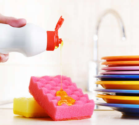 dishwashing: Several colorful plates, a kitchen sponges and a plastic bottle with natural dishwashing liquid soap in use for hand dishwashing. Eco-friendly, toxin-free, green cleaning product. Dishwashing concept.