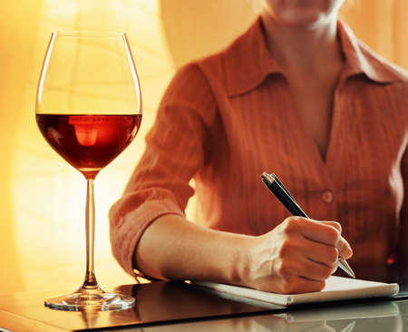 red taste: Glass of red wine for tasting in cafe. Woman sommelier making notes in notebook about color, aroma, taste, acidity, structure, texture, and balance of a wine.