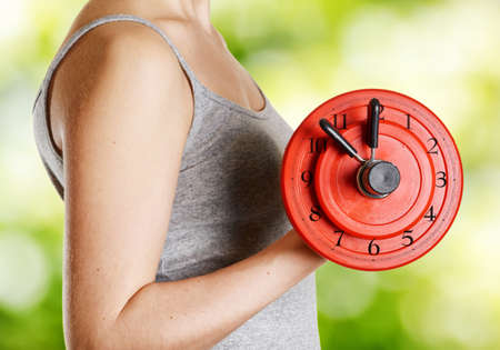 woman with clock: Beginner female athlete holding dumbbell with clock dial on nature background. Time for fitness. Trendy exercise for health, sexuality and building muscle without fat. Stock Photo