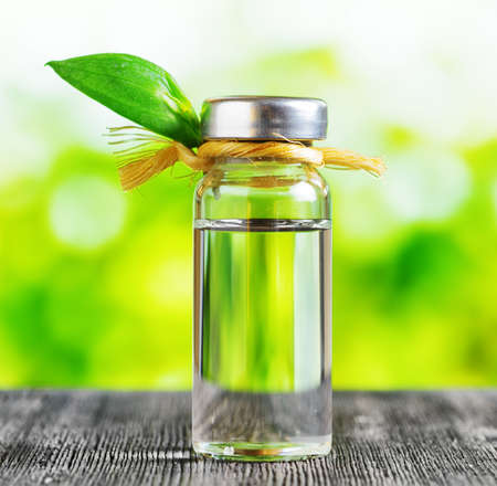 Vial of liquid on a black wooden table and on nature background. Aromatherapy and natural herbal medicine. Essential oils, effective skin care products, face and body products, spa treatments.