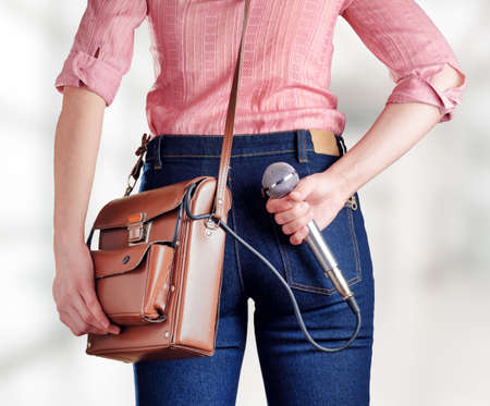 correspondent: Female journalist with microphone is preparing an unexpected question. Jeans and bag with a tape recorder inside in retro style. Stock Photo