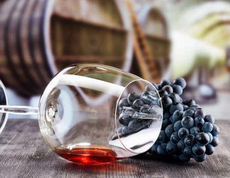 포도의 무리와 배럴 와인 셀러의 배경에 검은 나무 테이블에 누워 레드 와인의 유리.