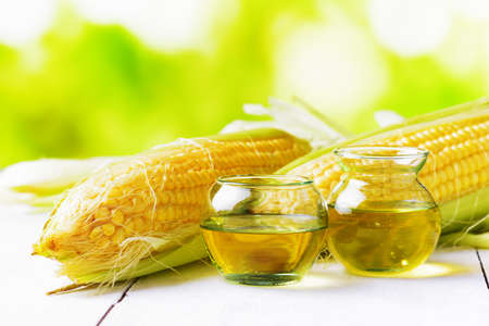 Corn oil and corn cobs on a garden table. Stock Photo