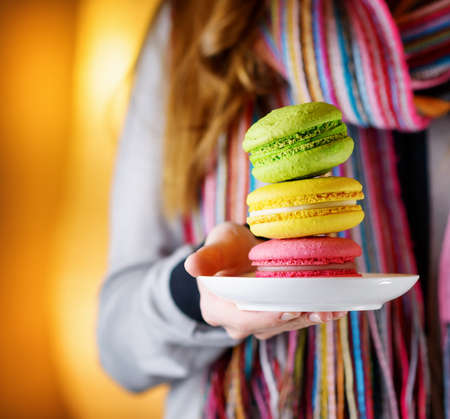 french cafe: Young woman holding the french pastry macaron on a white plate in cafe of Paris in France. Woman in fashionable colorful striped scarf. Hipster style. Trendy sweet confections. Stock Photo