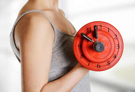 activity adult: Beginner female athlete holding dumbbell with clock dial. Time for fitness. Trendy exercise in gymnasium for health, sexuality and building muscle without fat. Stock Photo