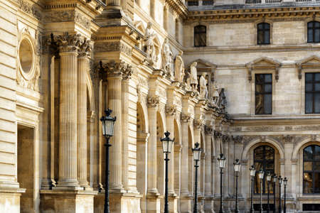 adorn: PARIS, FRANCE - AUGUST 13, 2014: Columns and sculptures that adorn the facade of the Louvre in Paris, France. Paris is one of the most popular tourist destinations in Europe.