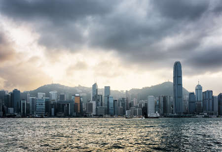 hong: View of Victoria harbor and skyscrapers in business center of Hong Kong Island with stormy sky. Hong Kong is popular tourist destination of Asia and leading financial centre of the world.