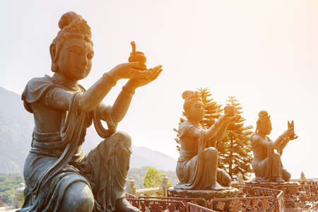 Buddhist statues praising and making offerings to the Tian Tan Buddha (the Big Buddha) in sunlight at Lantau Island, in Hong Kong. Hong Kong is popular tourist destination of Asia. Stock Photo