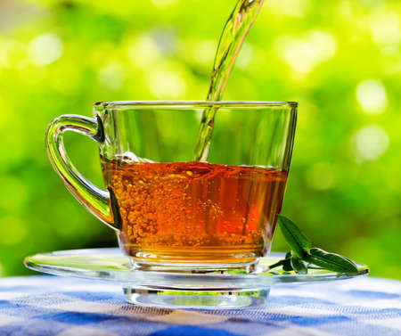 Invigorating fresh aromatic tea pouring into glass cup on the blue and white tablecloth in garden and on nature background.