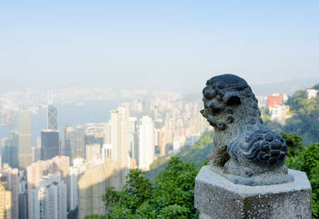 hong: Statue of a lion on the Victoria Peak and view of Hong Kong city in the background.