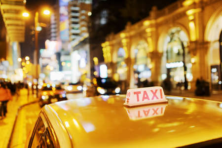 Closeup view of taxi on the street of elite stores at evening in Hong Kong. Hong Kong is popular tourist destination of Asia and leading financial centre of the world.