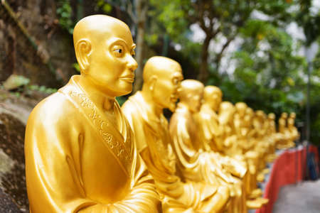 buddha face: Golden Buddha statues along the stairs leading to the Ten Thousand Buddhas Monastery and landscape with green trees in the background in Hong Kong. Hong Kong is popular tourist destination of Asia.