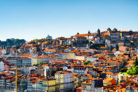 blue facades sky: Colorful facades and tile roofs of houses on the blue sky background, view of the historic centre of Porto in Portugal. Porto is one of the most popular tourist destinations in Europe.