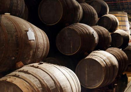 viñedo: Vino de Oporto de los viñedos del valle del Duero en Portugal envejecimiento en barricas de roble apilados en la antigua bodega oscura tradicional. Producto de la agricultura ecológica. Foto de archivo