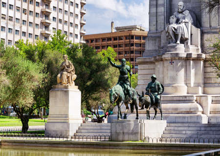 espana: The stone sculpture of Miguel de Cervantes and bronze sculptures of Don Quixote and Sancho Panza on the Square of Spain (Plaza de Espana) in summer. Madrid is a popular tourist destination of Europe. Stock Photo