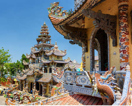 roof profile: The beautiful Linh Phuoc Pagoda in mosaic style from shards of glass, pottery and porcelain in Da Lat city (Dalat) on the blue sky background in Vietnam. Da Lat is a popular tourist destination of Asia.