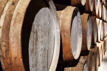oak: Closeup view of oak barrels stacked in the old cellar with aging Port wine from the vineyards Douro Valley in Portugal. Product of organic farming.