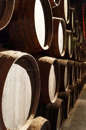 douro: Side view of oak barrels stacked in the old cellar with aging Port wine from the vineyards Douro Valley in Portugal. Product of organic farming.