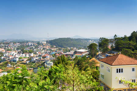 lat: House with tile roof and a beautiful view of Da Lat city (Dalat) on the blue sky background in Vietnam. Da Lat is a popular tourist destination of Asia.